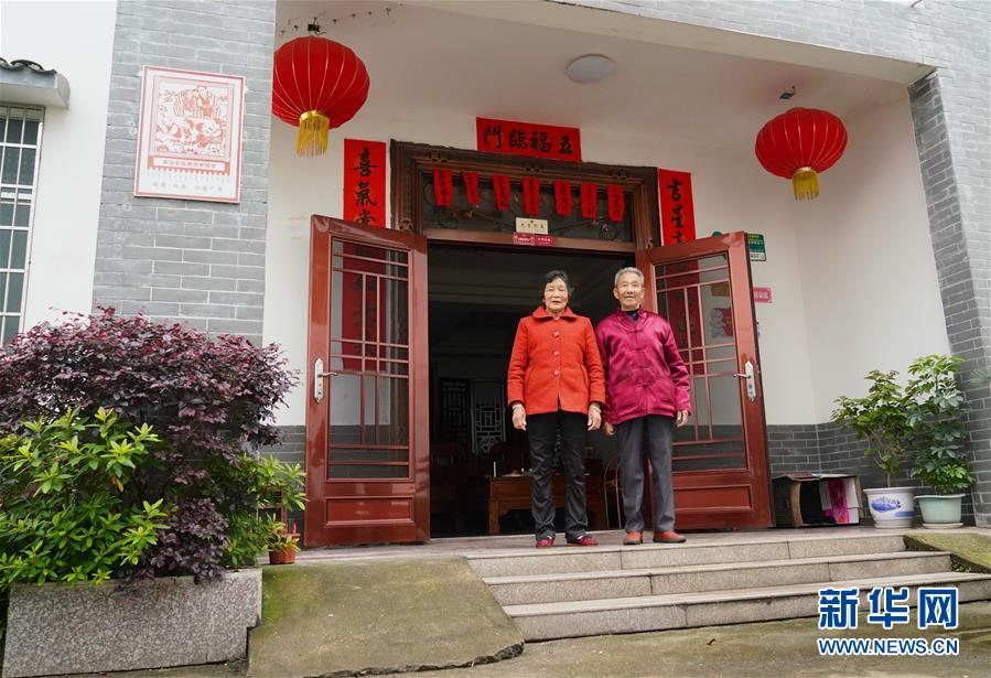 5月7日,江西瑞金华屋村居民华从祁和妻子在新家门前留影。 新华社记者 胡晨欢 摄