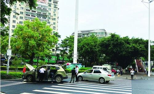车行工作人员在路口占地清理车辆,导致车主回家的路受阻。