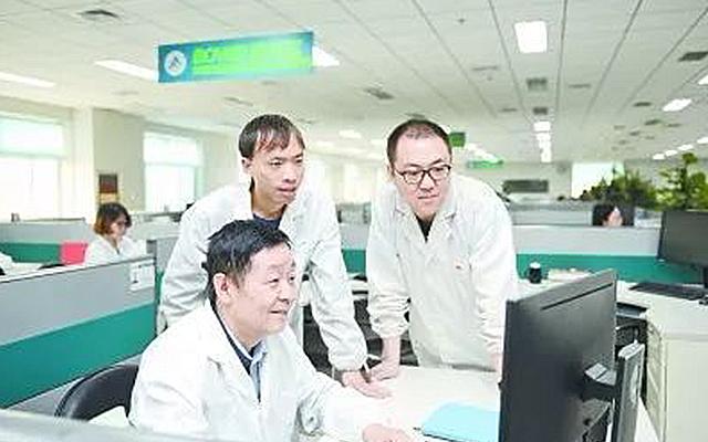 要志宏(左一)查看设计方案
