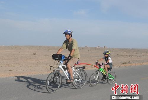 2009年,古丝绸之路骑行过程中遇到困难路段,陈守忠用拖车棒领着陈萱骑行。中新社发 陈守忠 供图