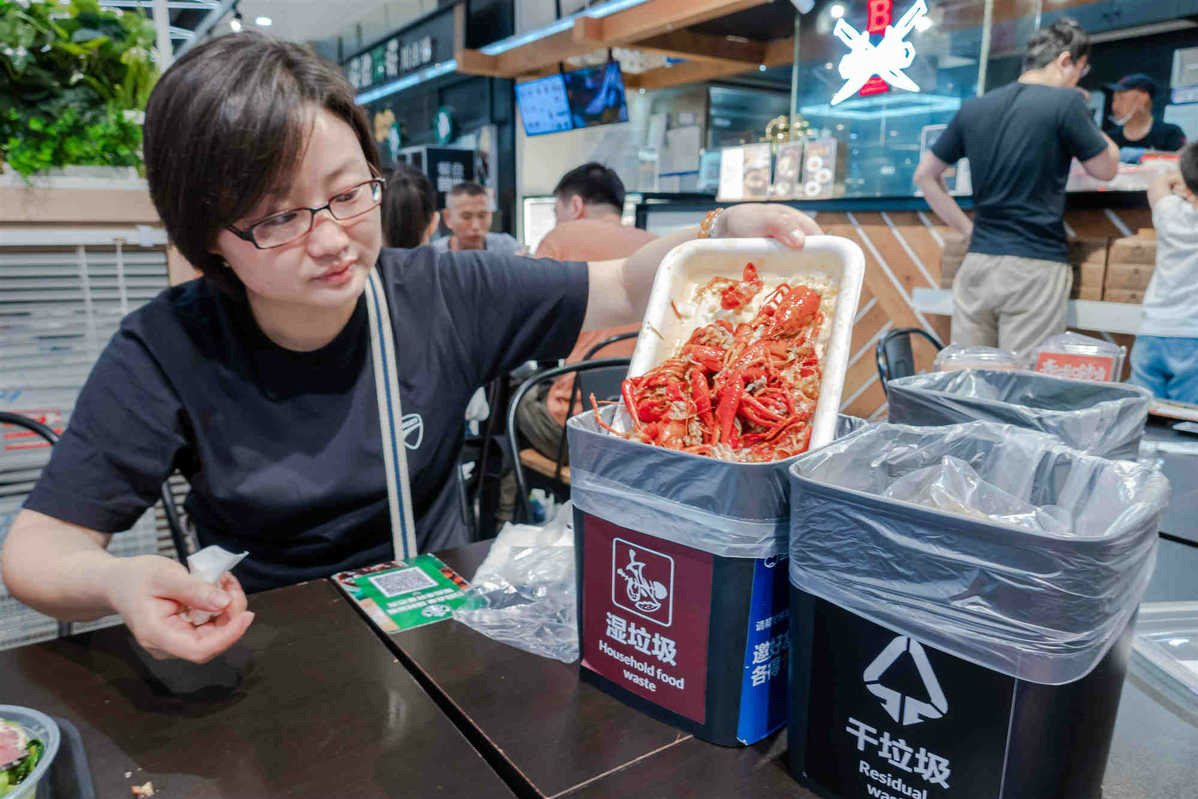 A customer sorts trash at a seafood diner in Shanghai on Sunday. [Photo by Wang Gang/ For China Daily]