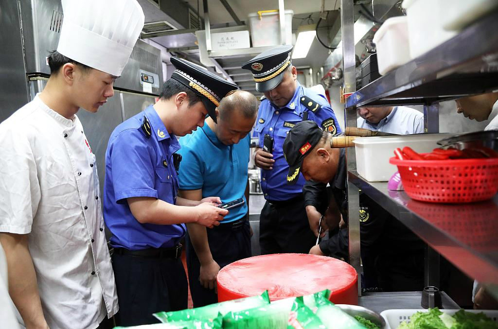 Law enforcement officers inspect the waste sorting at a restaurant in Shanghai on Sunday. [Photo/VCG]