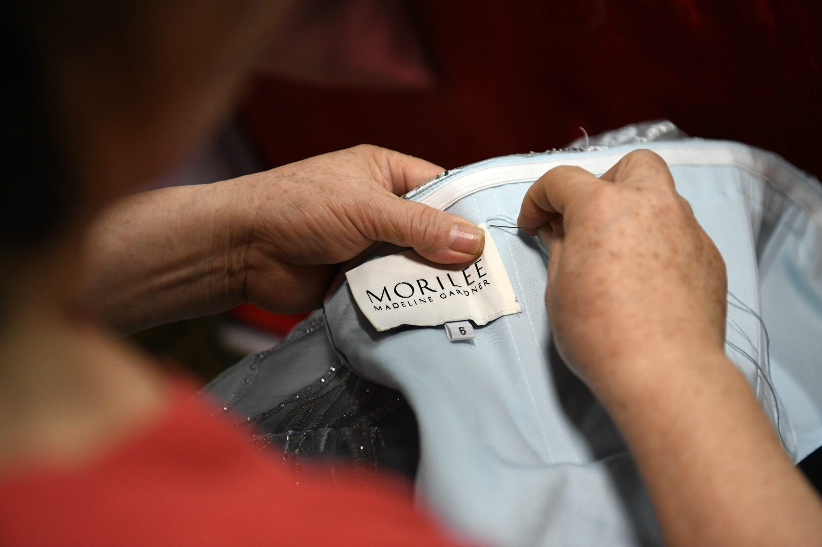 An embroiderer sews a brand label onto a Morilee dress at a factory in Chaozhou, south China