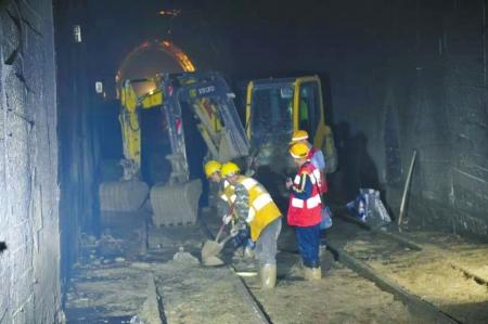 前两次铁路中断之后,抢险人员在隧道内抢险。