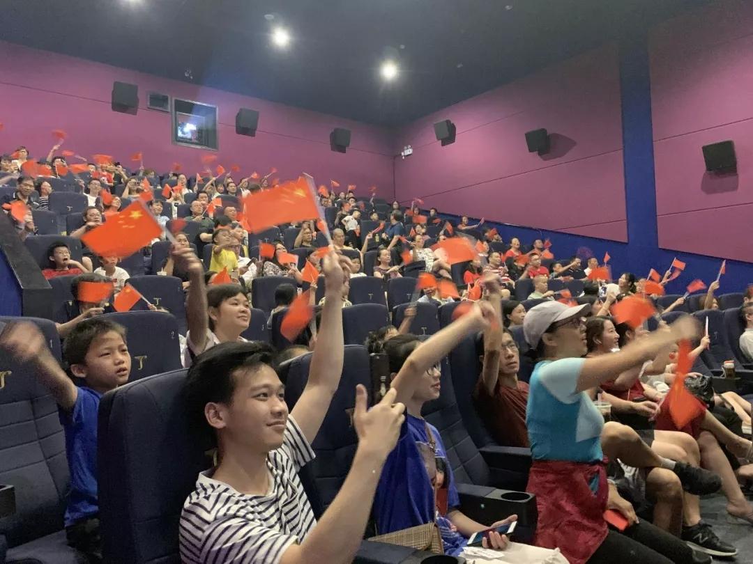 广州某影厅,观众挥舞国旗等待直播开始。