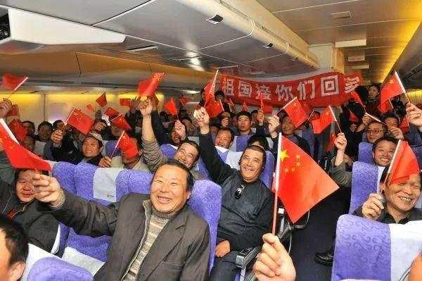 资料图片:2011年3月5日,在利比亚撤侨航班上,中国同胞手举国旗庆祝。 这是空军首次派运输机赴海外执行撤离我人员回国任务。