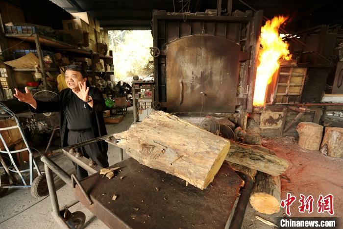 图为何志隆在窑旁向记者介绍烧制过程。中新社记者 张远 摄