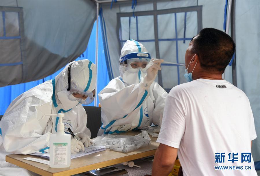 6月18日,在海淀区区级核酸检测采样点,医护人员为市民进行核酸检测采样。 新华社记者 任超 摄