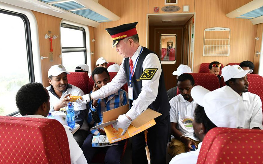 Li Chenglin (C), head of the train crew, gives cookies to passengers on a passenger train of Ethiopia-Djibouti railway in Ethiopia, on Oct. 5, 2016.