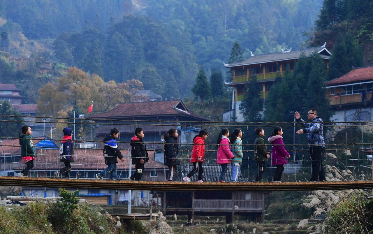 一位驻村工作队队员带领小朋友们参观新建成的铁索桥 黄孝邦 摄